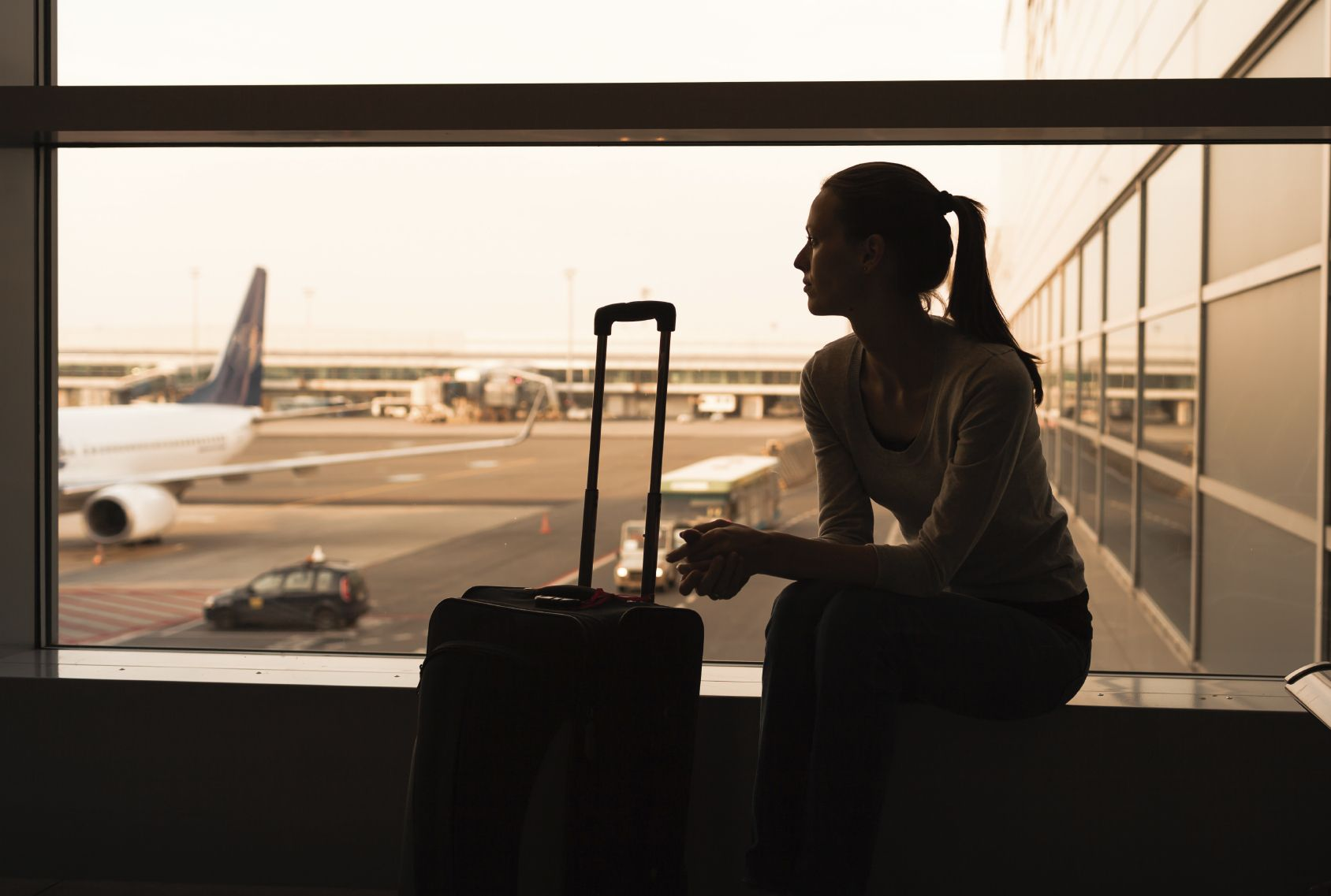 A woman with her suitcase looking at the window in an airport